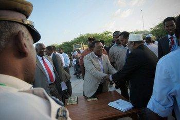 Special Representative Augustine Mahiga greets a Somali official ahead of the inauguration ceremony in Mogadishu.