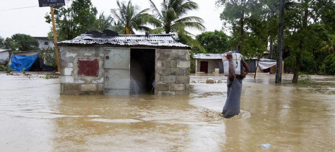 A resident of a low-lying area of Port-au-Prince flees his flooded home taking whatever possessions with him.