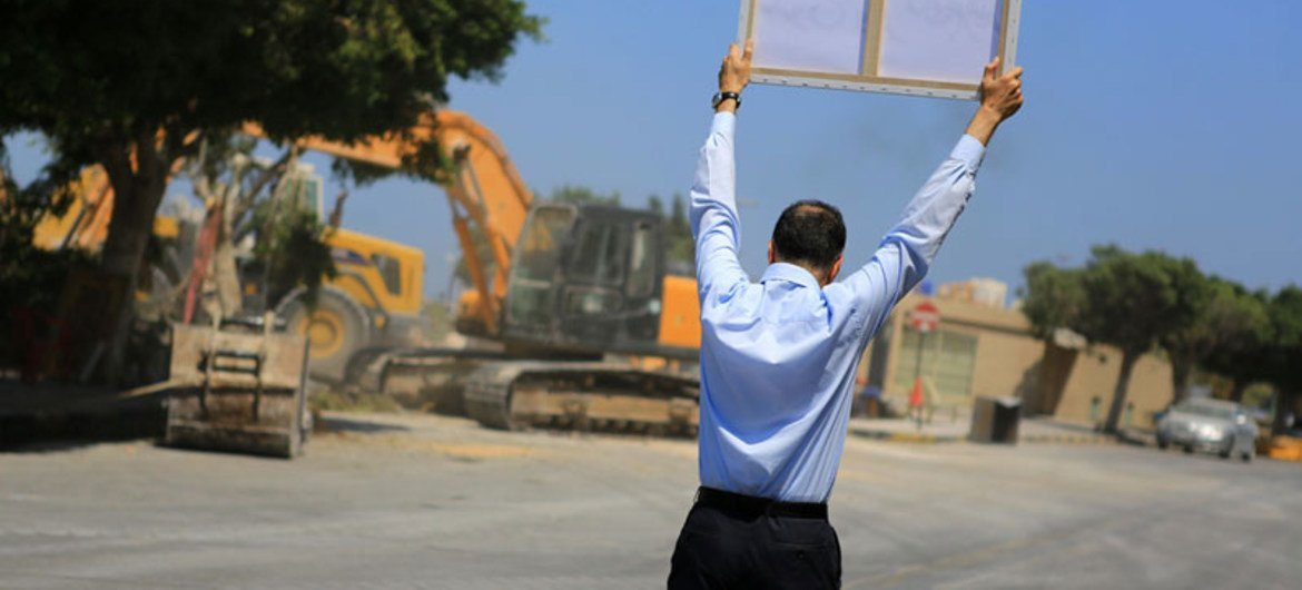 A lone protester holds up a placard condemning the destruction of a Sufi shrine in Tripoli as he approaches the site of the demolition.