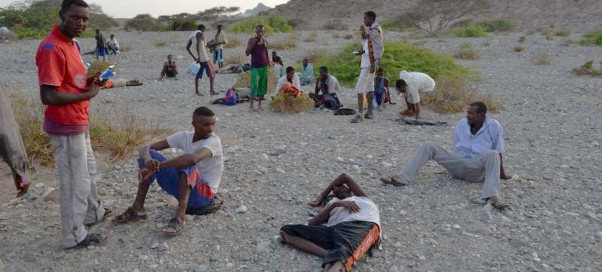 Exhausted new arrivals recover on a beach after crossing the ocean to southern Yemen.