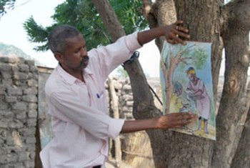 Health worker during community awareness campaign, showing guinea worm disease flipchart.