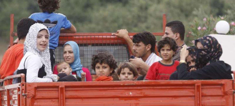 Une famille syrienne franchit la frontière avec le Liban pour rejoindre un centre d'enregistrement du HCR.