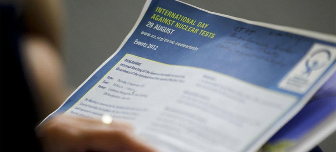 A participant looks over the programme of the General Assembly's informal meeting on the International Day against Nuclear Tests.