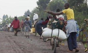 People flee their homes as fighting continued between FARDC and M23 rebels in the Rutshuru territory in July 2012.