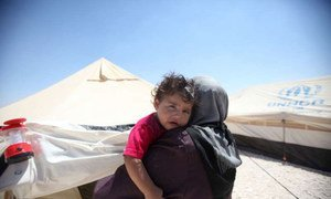 A Syrian refugee woman holds her child in Jordan's Zaátri camp, where the needs are many.