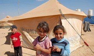 Des enfants syriens devant une tente du HCR, dans le camp de réfugiés de Za'atri, situé en Jordanie.