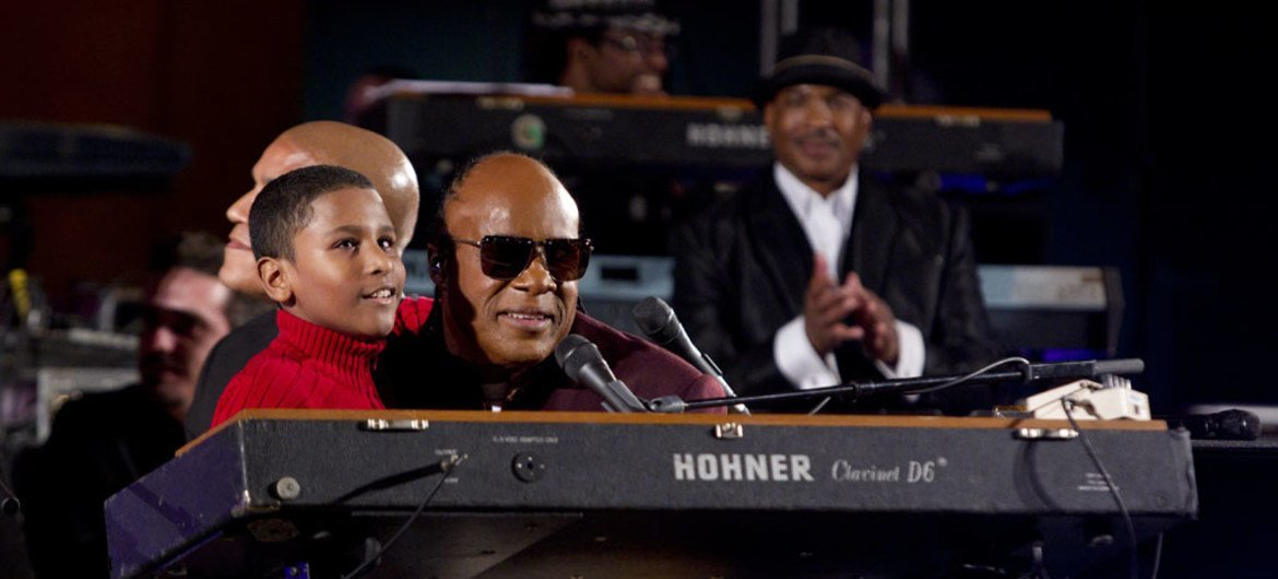 """A blind boy named Emmanuel joins American singer and UN Peace Messenger, Stevie Wonder, who is also blind, on stage during the UN Day Concert, """"A Message of Peace."""""""