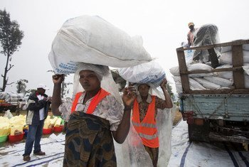 At the Kanyaruchinya internally displaced persons camp in Goma, women carry large bags of food rations distributed by UNICEF.