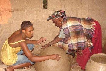 Mmasekgwa Motlhware transmet à sa petite-fille Tumediso le savoir-faire de la poterie en terre cuite dans le district de Kgatleng au Botswana.
