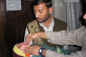 Un enfant pakistanais reçoit des gouttes contre la poliomyélite.