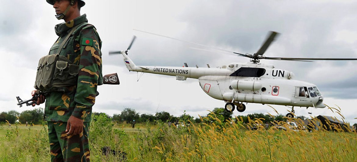 A UN peacekeeper in South Sudan with one of the mission's helicopters.