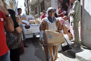 Une femme à Damas, en Syrie, reçoit des rations alimentaires de la part du PAM.