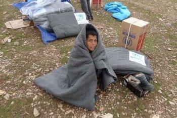 Un jeune réfugié syrien tente de se réchauffer à l'aide d'une couverture au nord de l'Iraq.