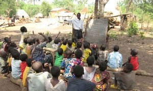 Children displaced by violence in the Central African Republic (CAR) attend an open-air class at a camp.