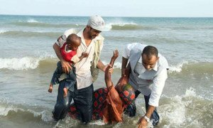 Aid workers from a UNHCR partner organization help people who have just reached the Yemeni shore by boat.