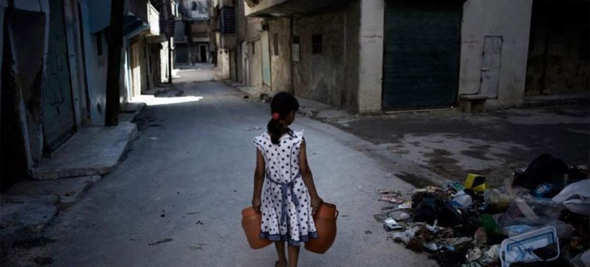 A girl carrying jerrycans of water, walks past a pile of debris on a street in Aleppo, Syria. UNICEF/NYHQ2012-1293/Romenzi