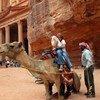 Turistas subiéndose a un camello en Petra, en Jordania.