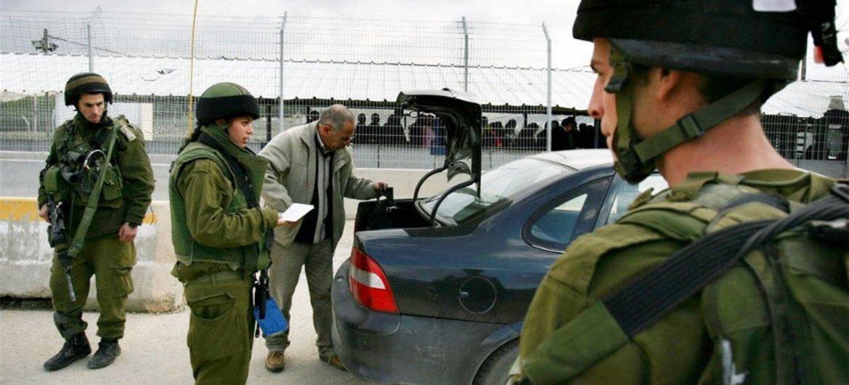جنود اسرائيليون يفتشون سيارة فلسطينية عند نقطة تفتيش حوراة خارج مدينة نابلس في الضفة الغربية.