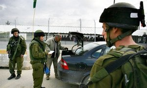 Israeli soldiers search a Palestinian's car at the Hawera checkpoint outside the town of Nablus in the West Bank.
