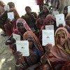 Dalit Women on the outskirts of Chakrapanpur Village, Varanasi District, Uttar Pradesh, display  job cards.