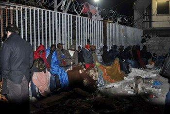 Des files d'attentes de migrants dans une rue d'Athènes, en Grèce.