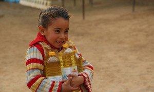 Une petite syrienne porte des bouteilles d'huile fournies par le PAM.