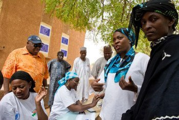 Le Directeur exécutif du Programme alimentaire mondial (PAM), au cours d'une visite dans le village de Tolkobey, au Niger, où des mères allaitantes se voient remettre des céréales enrichies.