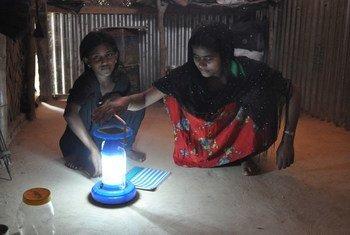 Une réfugiée et sa fille se servent d'une lampe solaire.