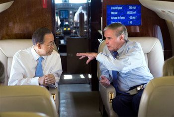 Secretary-General Ban Ki-moon (left) chats with Ray Chambers,  Special Envoy for Malaria, during a flight to Thailand (Nov 2011).