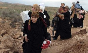 A line of Syrian refugee women, some carrying children, cross into Jordan from southern Syria.