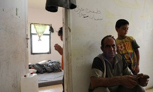 A boy and his father in Cyber City, a transit facility for Syrian refugees, in Ramtha, Jordan.