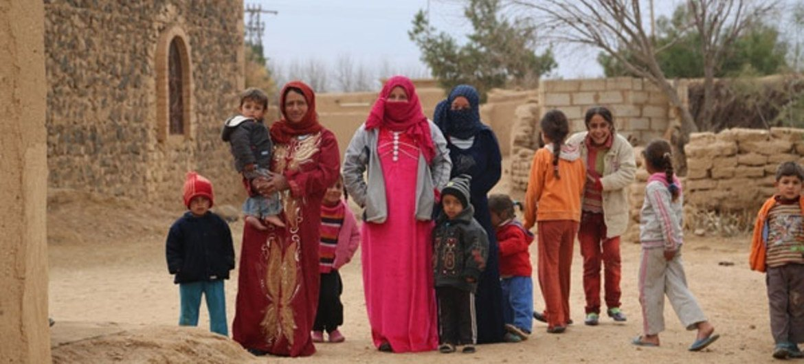 Displaced persons in Al-Shadadi district in Al-Hassakeh, northeast Syria, wait for WFP food trucks that bring them their monthly food rations.