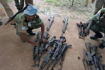Soldado da paz em Côte d'Ivoire com armas de fogo apreendidas