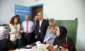 High Commissioner for Refugees António Guterres (in tie) and UNHCR staff talking to Syrian women.