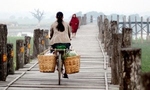 A woman rides a bicycle to work in Myanmar's second city, Mandalay