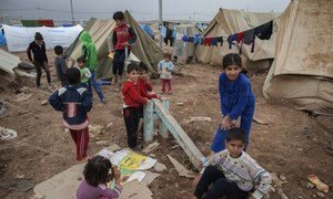 Displaced Syrian children play among tents at the Domiz refugee camp.