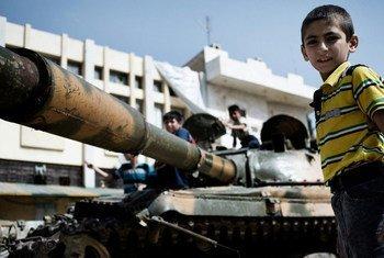 Des garçons jouent autour d'un tank détruit de l'armée syrienne, au nord-ouest d'Alep.