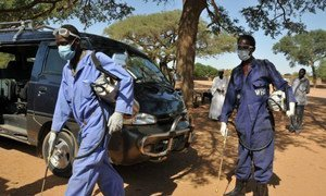 Health workers carrying out a spraying operation to eradicate infected Anopheles mosquitoes which spread malaria.