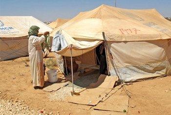 Une réfugiée syrienne  suspend son linge devant sa tente dans le camp de Za'atari en Jordanie