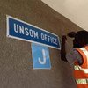 सोमालिया में संयुक्त राष्ट्र सहायता मिशन का बोर्ड ठीक करता एक कर्मचारी.