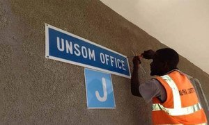 A worker putting up a sign for the new UN Assistance Mission in Somalia (UNSOM) Headquarters in Mogadishu.