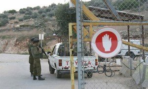 Israeli soldiers inspect a vehicle entering the village of Azzun Atma through the West Bank Barrier.