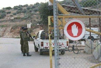 جنود اسرائيليون يقومون بالتحقق من سيارة دخلت عن طريق الجدار العازل في الضفة الغربية. من صور: إيرين / توم سبندر