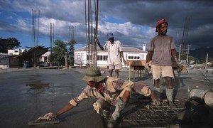 Des ouvriers étalant du ciment sur un toit.