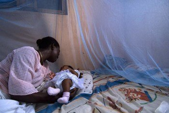 Infant surrounded by protective malaria bed net in Ghana.