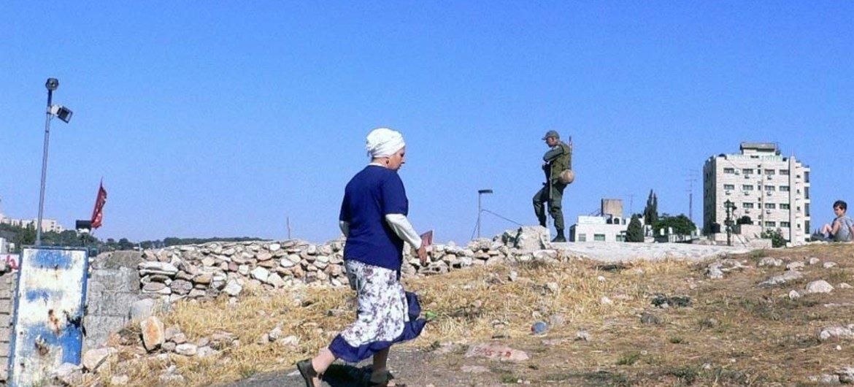 A settler woman walks past an Israeli soldier standing guard in East Jerusalem.