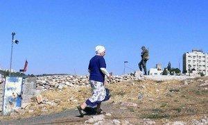 Une habitante d'une colonie passe à proximité d'un soldat israélien à Jérusalem-Est.