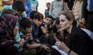 UNHCR Special Envoy Angelina Jolie (right) records the stories of refugees who have just escaped the war in Syria at the Jaber border crossing in Jordan on 18 June 2013.
