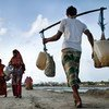 Above, people carry drinking water in Bangladesh.