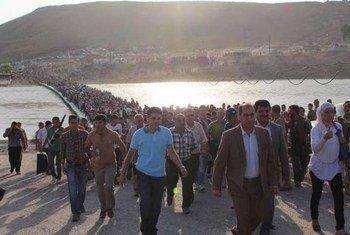 Des milliers de Syriens franchissent la frontière avec l'Iraq par un pont sur le Tigre.